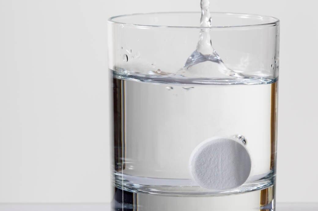 Eine Magnesiumtablette löst sich in einem Glas Wasser auf