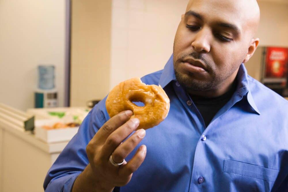 Mann isst Donut