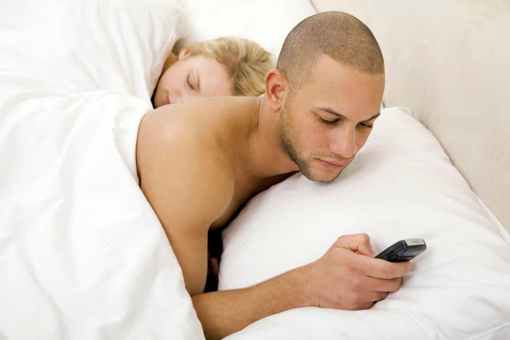 Junger Mann mit Handy im Bett