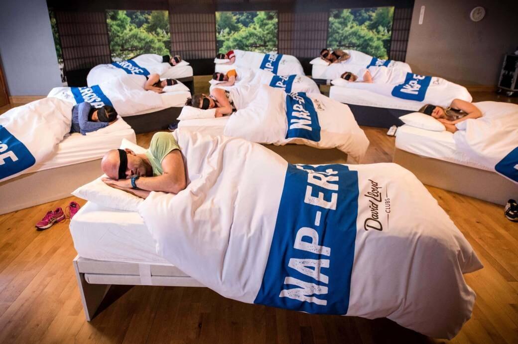 Eine Gruppe von Menschen hat sich in einem Fitnessstudio zu einem Napercise-Schalfkurs zusammengefunden