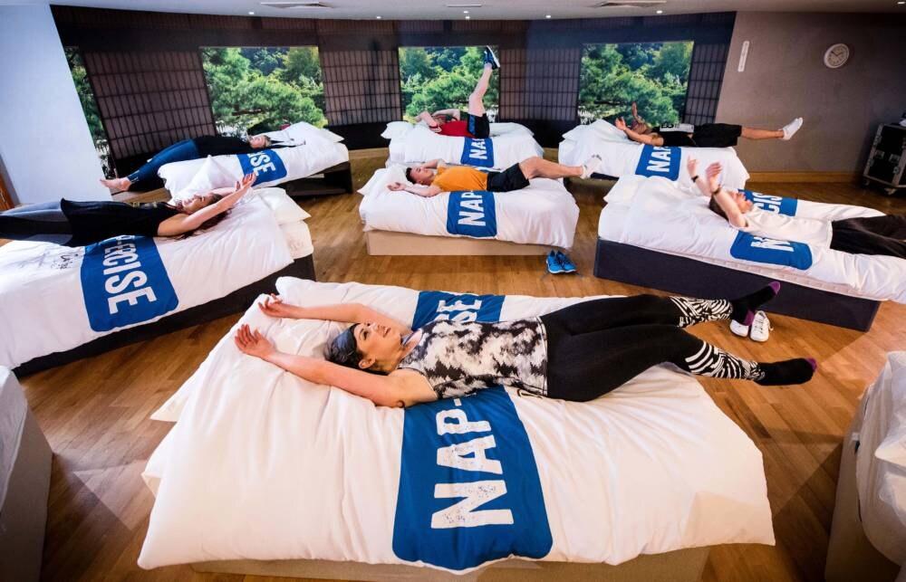 Kursteilnehmer lassen sich beim Napercise auf ein Bett fallen