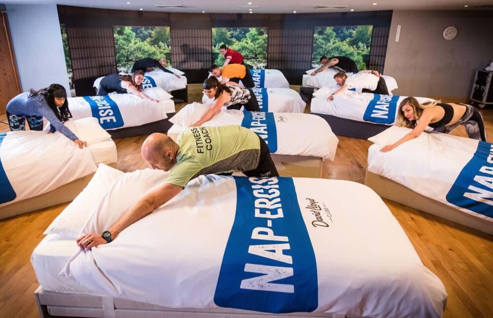 Ein Fitnesstrainer zeigt dem Kurs eine Übung beim Napercise