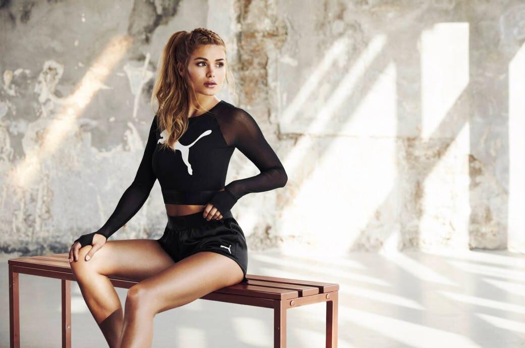 Pamela Reif sitzt in Sportswear auf einer Bank