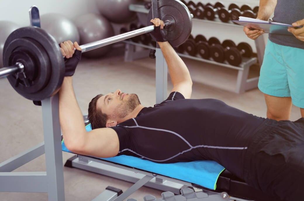 Ein Mann trainiert mit Handschuhen an Gewichten im Fitnessstudio