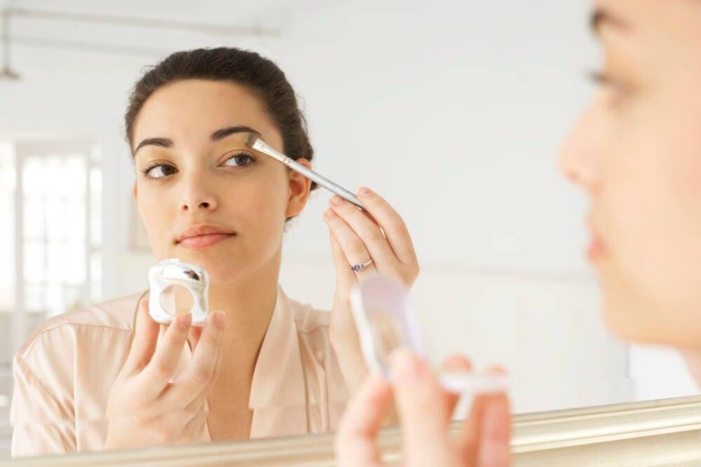Eine junge Frau trägt vor einem Spiegel Make-up auf