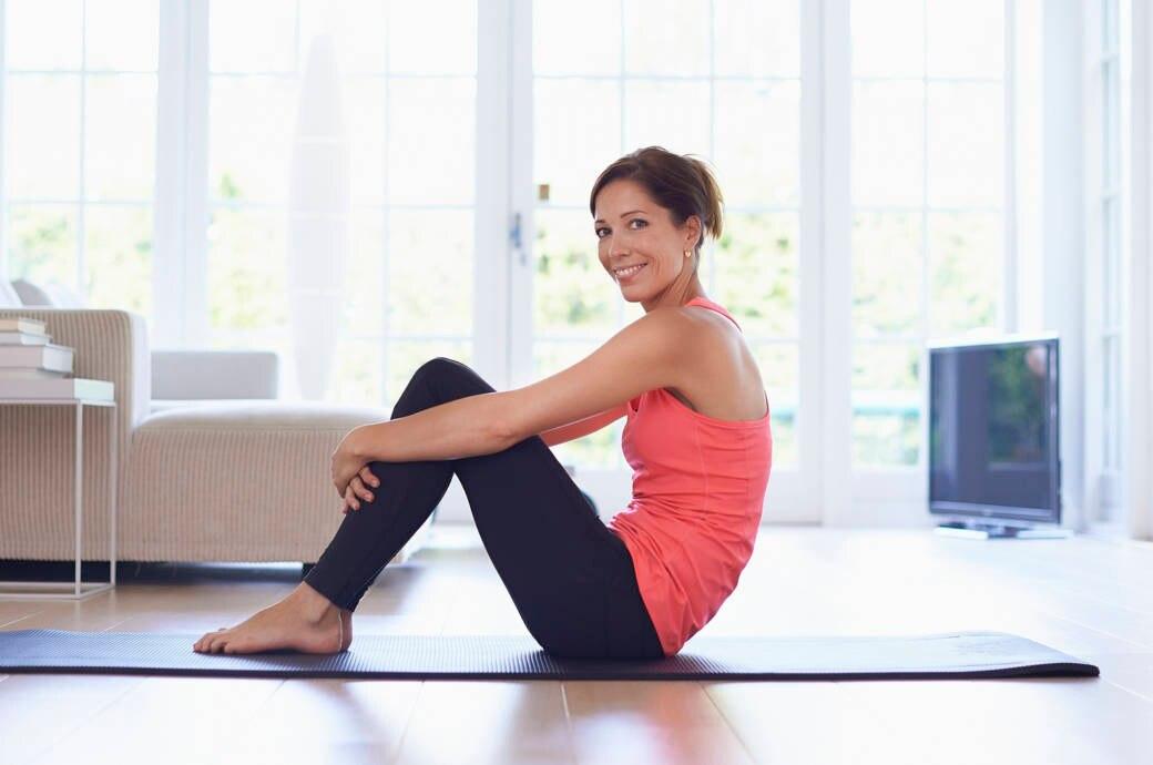 eine sportlich gekleidete junge frau sitzt auf dem boden. Black Bedroom Furniture Sets. Home Design Ideas
