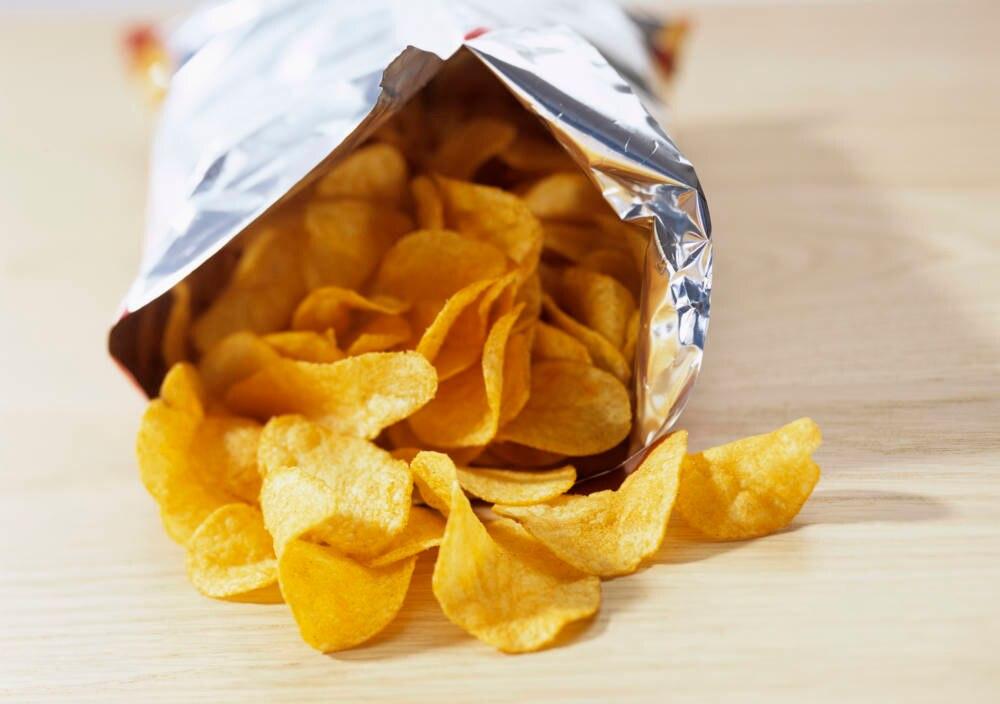 Eine offene Tüte Kartoffelchips liegt auf einem Tisch