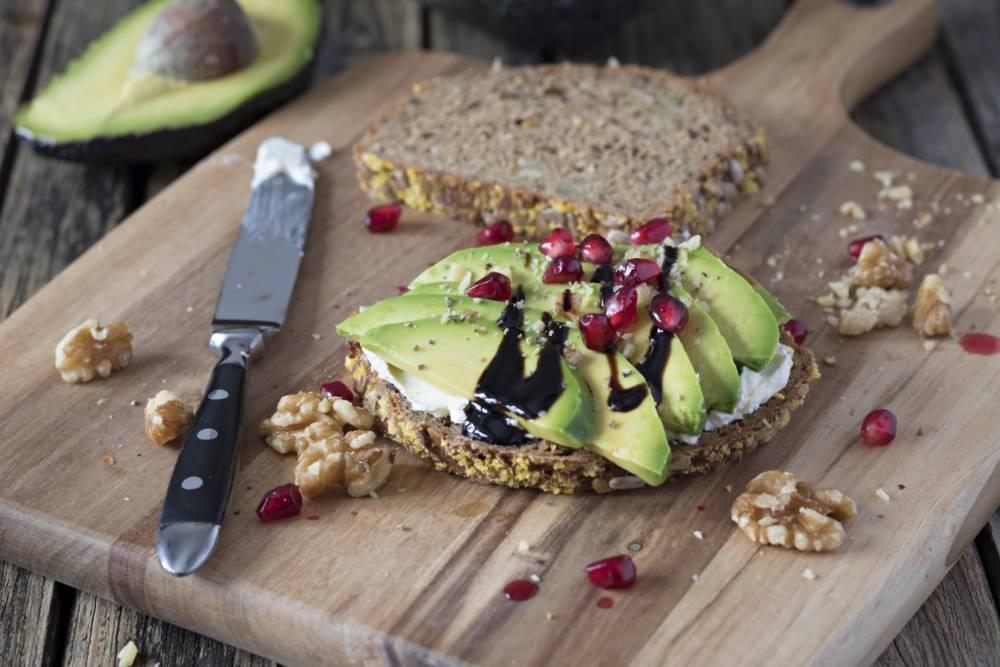 Avocadoscheiben auf Eiweißbrot mit Frischkäse, Walnüssen und Granatapfelkernen auf einem Holzbrett