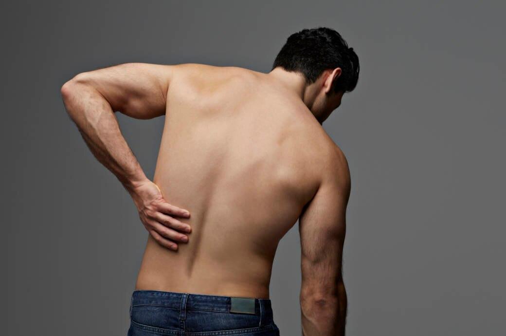 Ein junger Mann hält sich schmerzend den Rücken