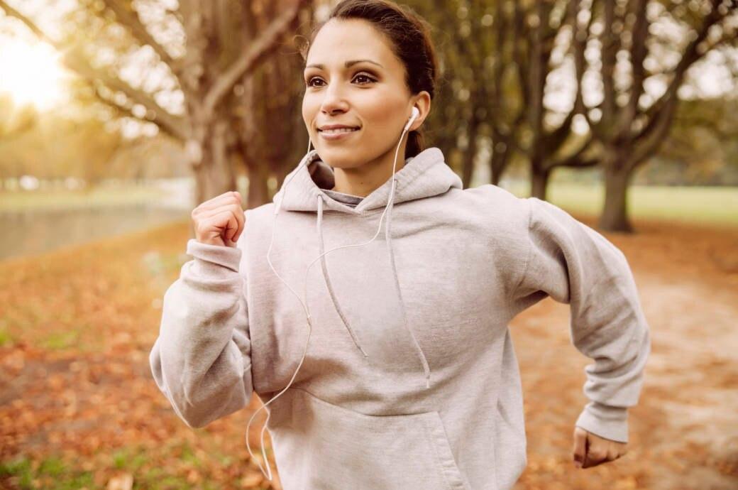 Eine junge Frau läuft durch einen herbstlichen Park