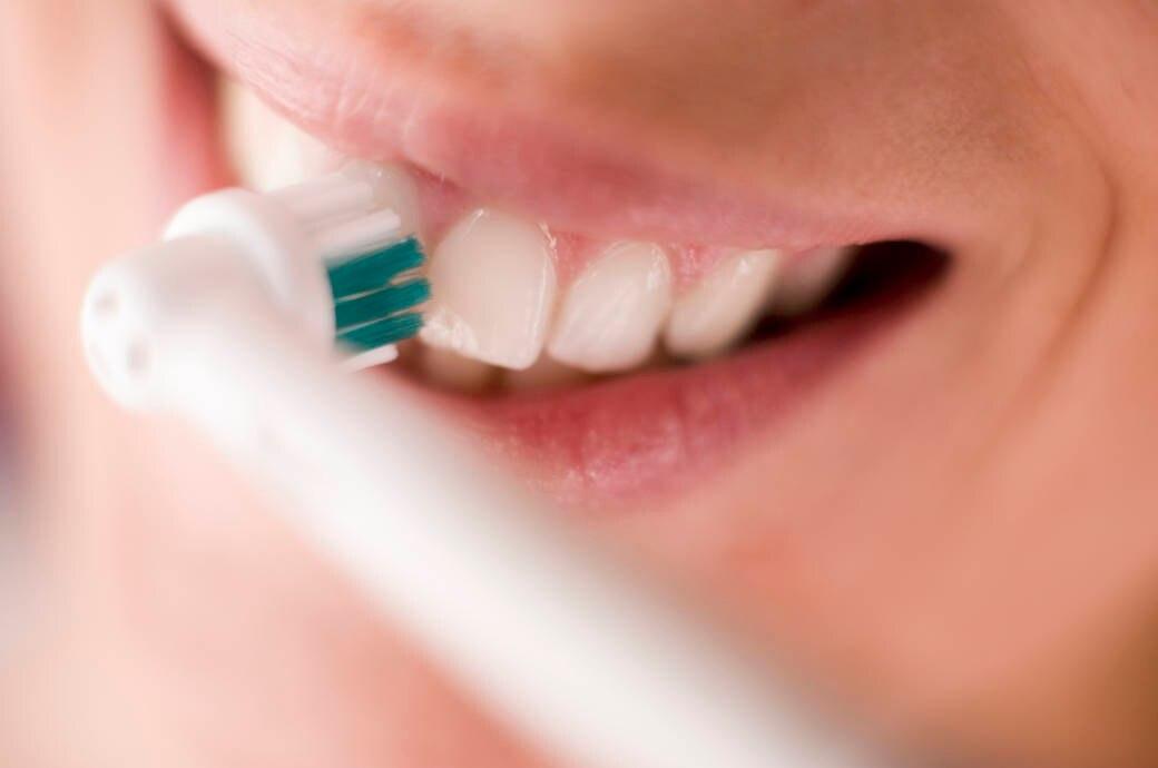 Frau putzt sich die Zähne mit einer elektrischen Zahnbürste