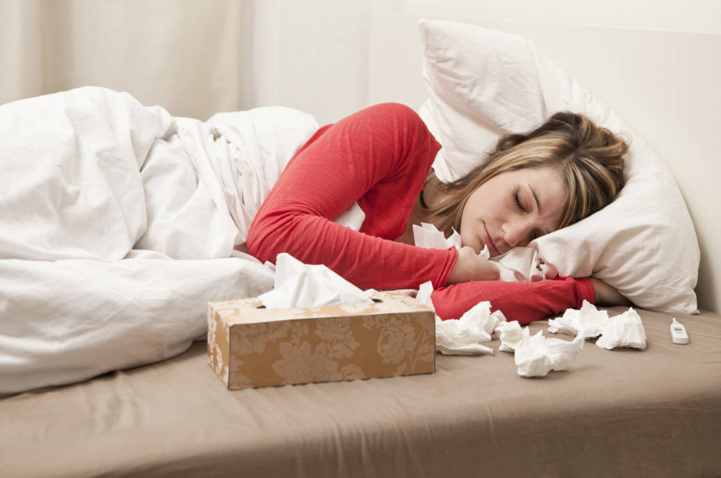 Eine junge Frau liegt mit Schnupfen im Bett und schläft
