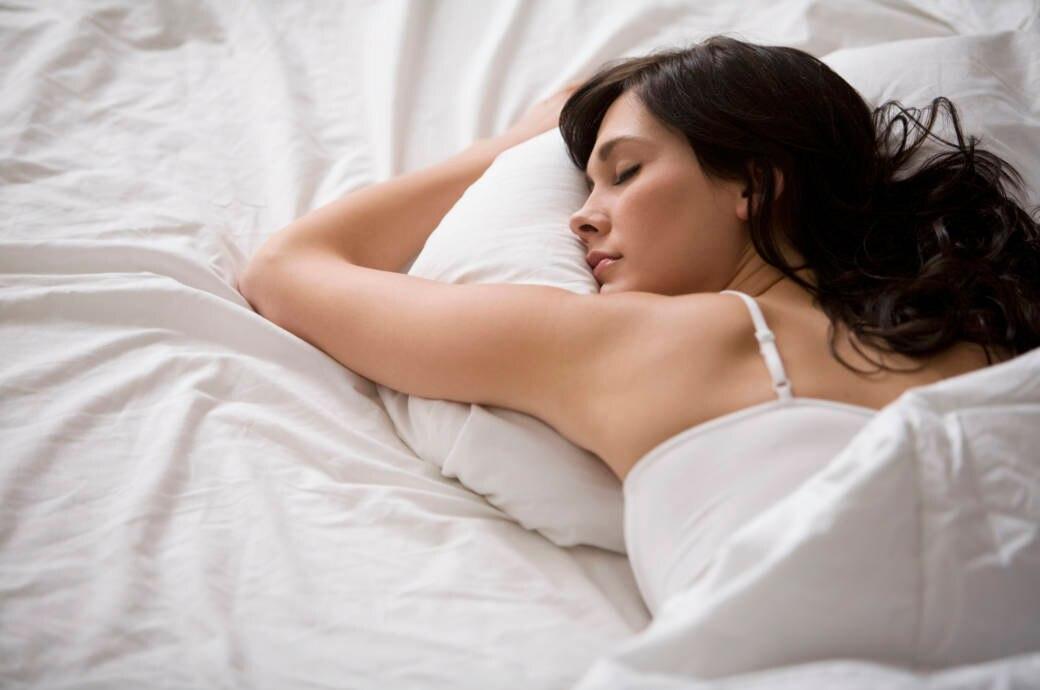 Eine junge Frau liegt im Bett und schläft.