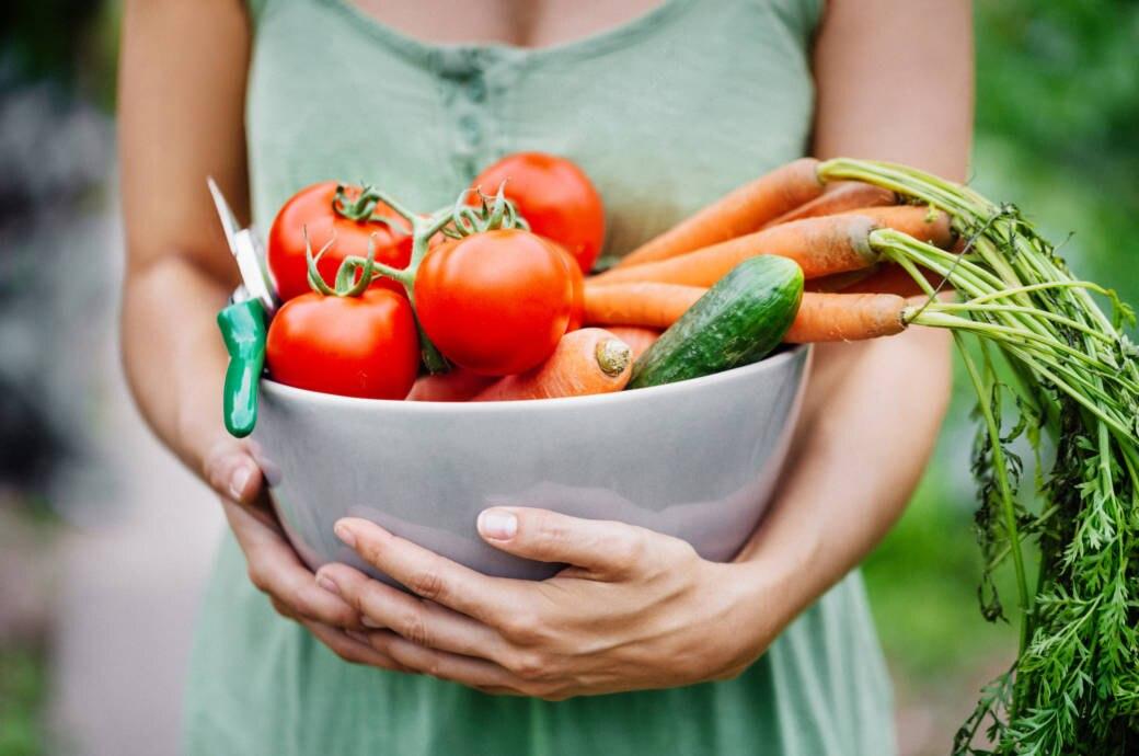 Frau hält Gemüsekorb in ihren Armen