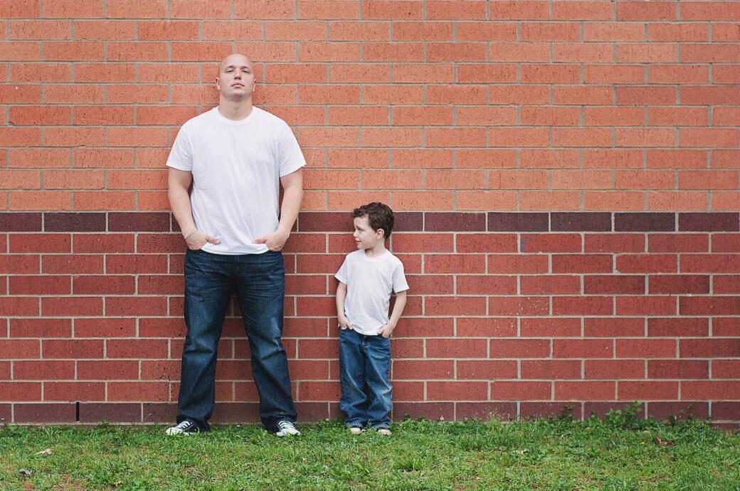 Vater und Sohn stehen ähnlich gekleidet an einer Wand