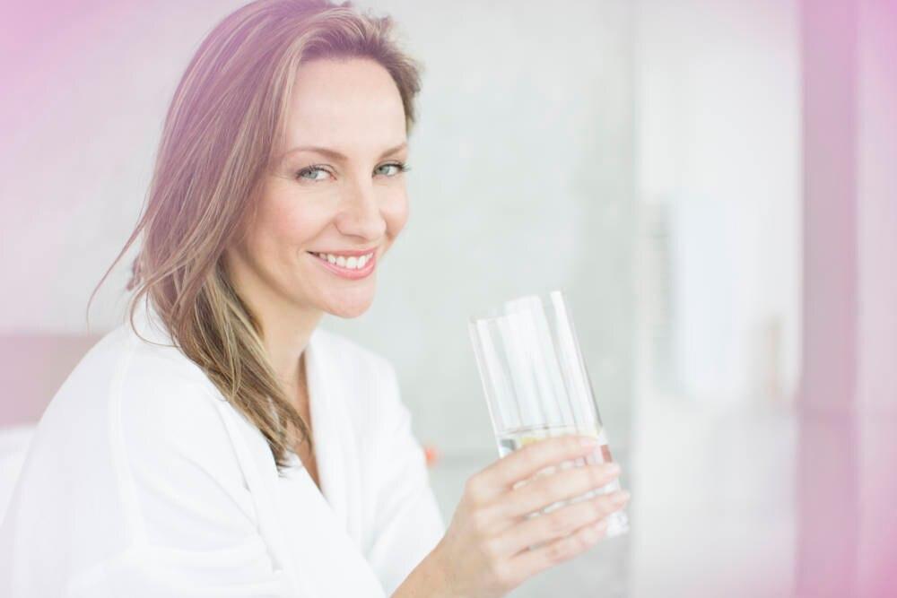 Eine junge Frau trinkt aus einem Glas
