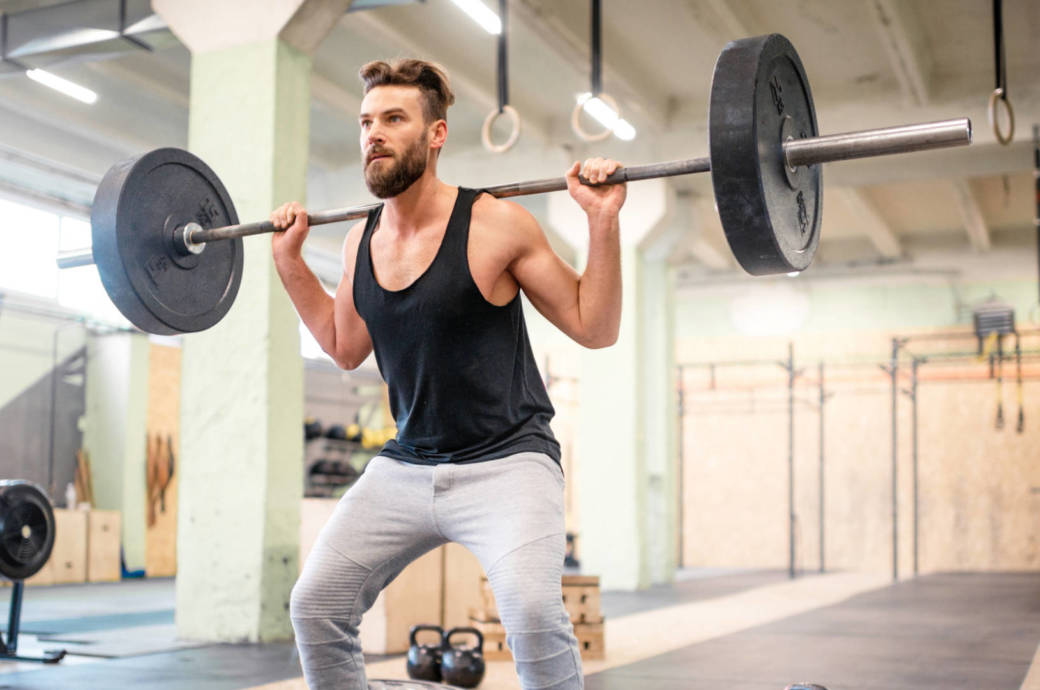 Ein junger Mann macht Kniebeugen mit zusätzlichem Gewicht