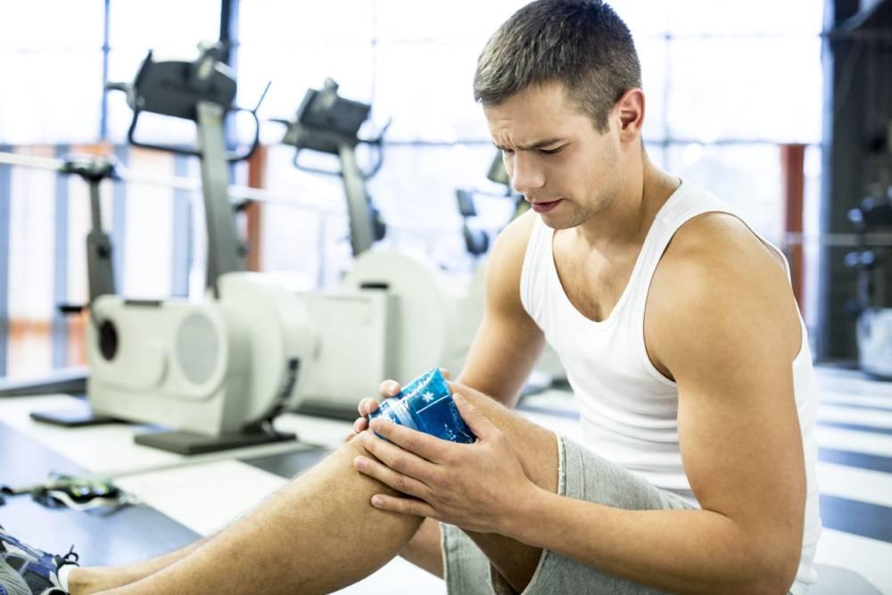 Ein junger Mann kühlt sein schmerzendes Knie