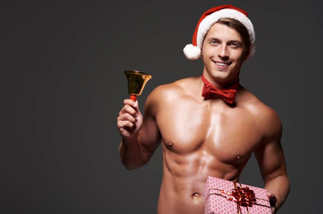 Gutaussehender und durchtrainierter, junger Mann steht oberkörperfrei und mit Weihnachtsmütze vor einem schwarzen Hintergrund und hat in der einen Hand ein Glöckchen und in der anderen ein rot verpacktes Geschenk.