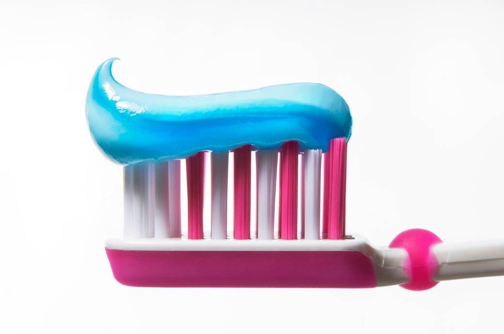 Pinke Zahnbürste mit blauer Zahnpasta