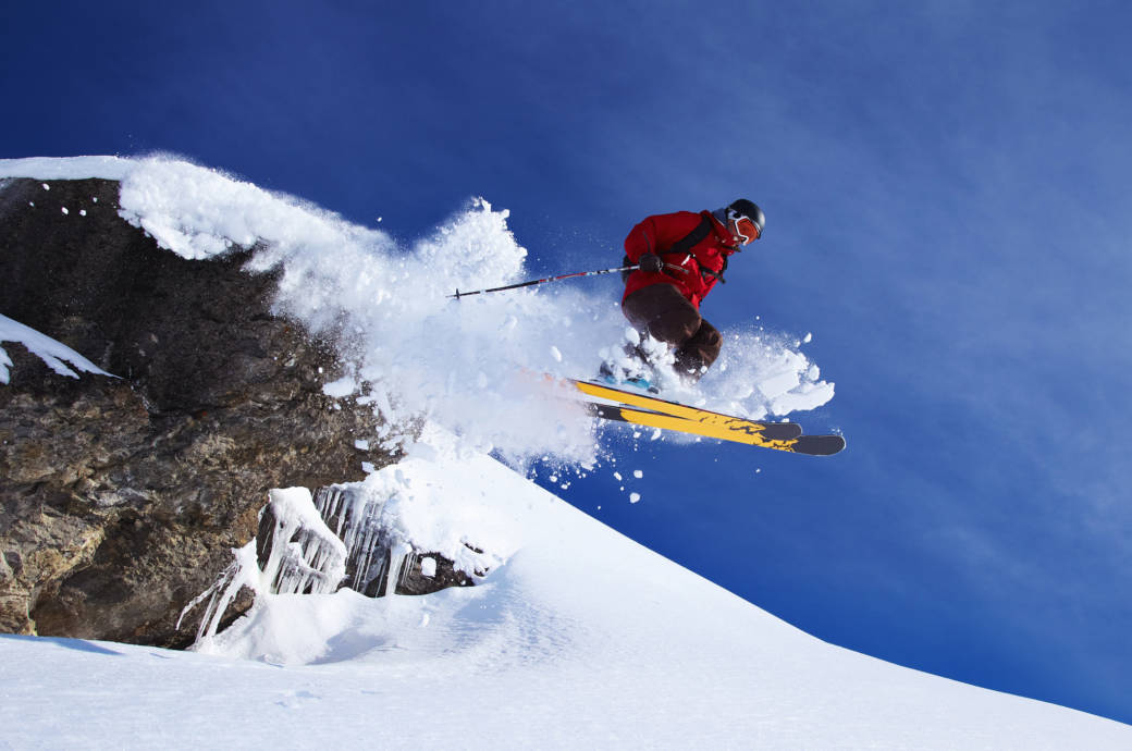 Ein Skifahrer springt über einen Felsvorsprung