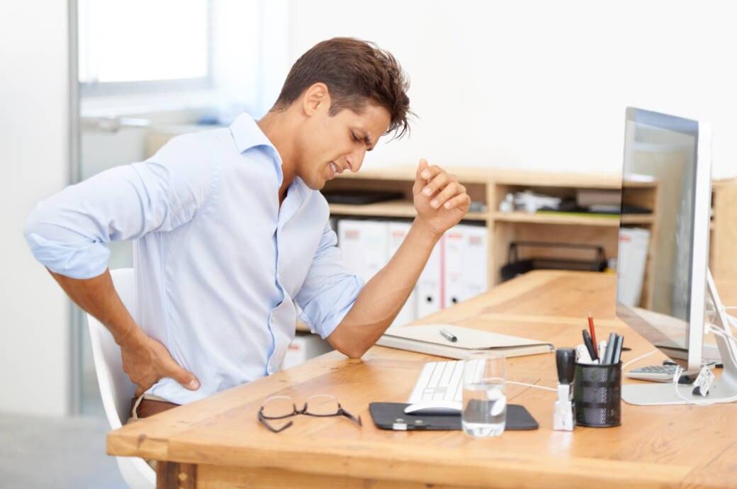 Ein junger Mann sitzt an einem Schreibtisch und hält sich mit schmerzverzerrtem Gesicht den unteren Rücken