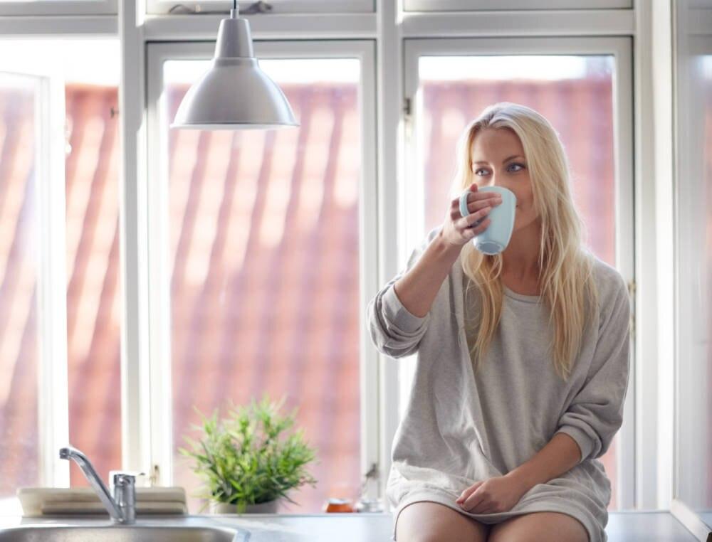 Eine junge Frau sitzt auf der Fensterbank ihrer Wohnung und trinkt ein Glas Wasser