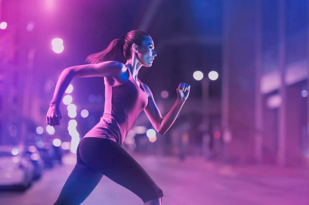 Eine junge Frau joggt nachts durch die Stadt