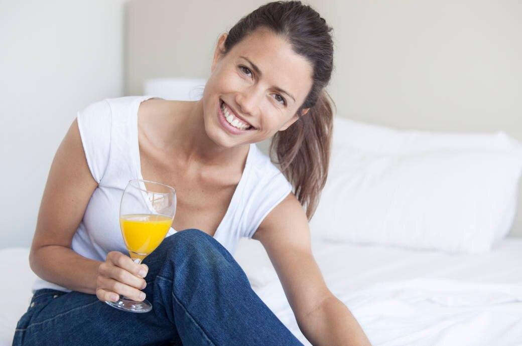 Eine junge Frau mit einem Sektglas voller Orangensaft