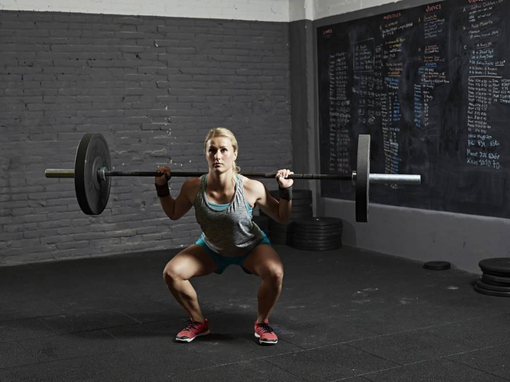 Frau macht Kniebeuge mit Langhantel zum Muskelaufbau