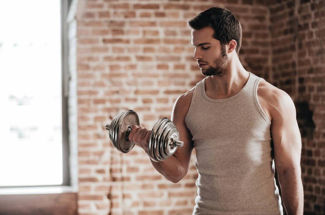 Ein muskulöser junger Mann trainiert mit einer Hantel in seiner rechten Hand