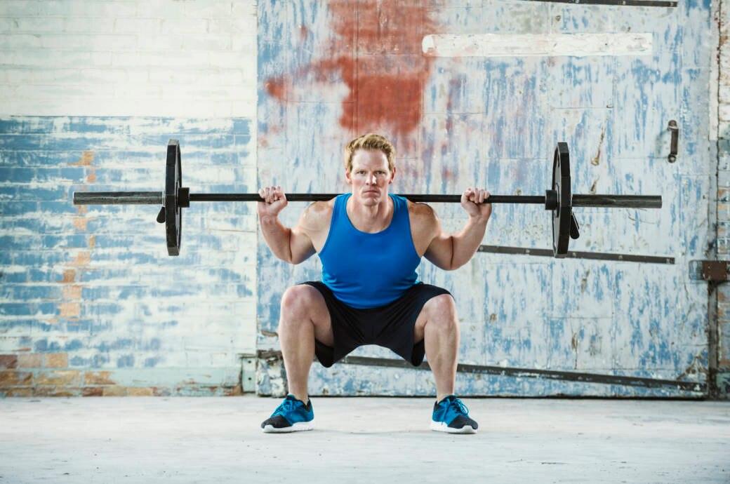 Mann macht Kniebeuge mit Gewicht
