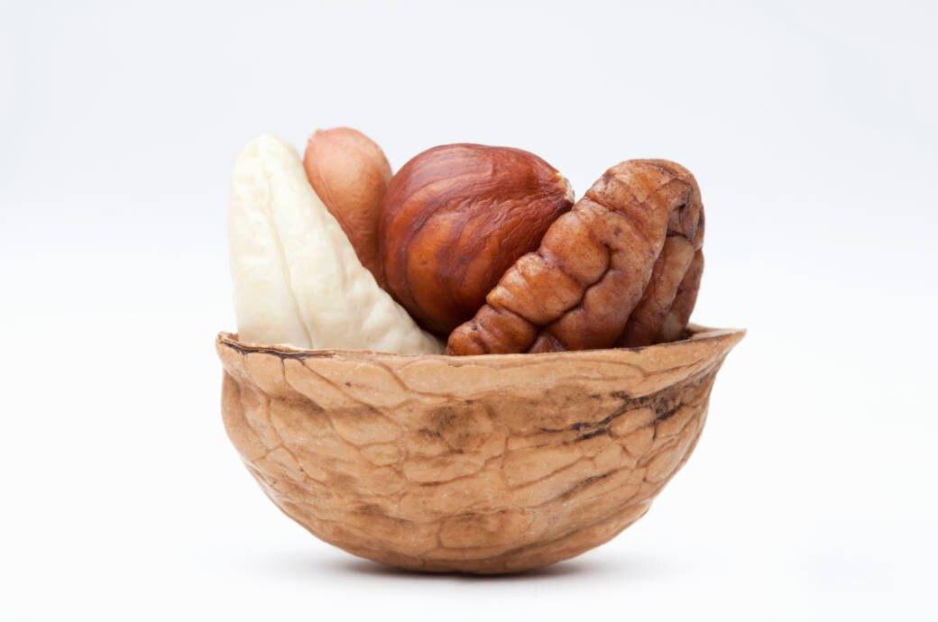 Ein Auswahl von Nüsse in einer Walnussschale