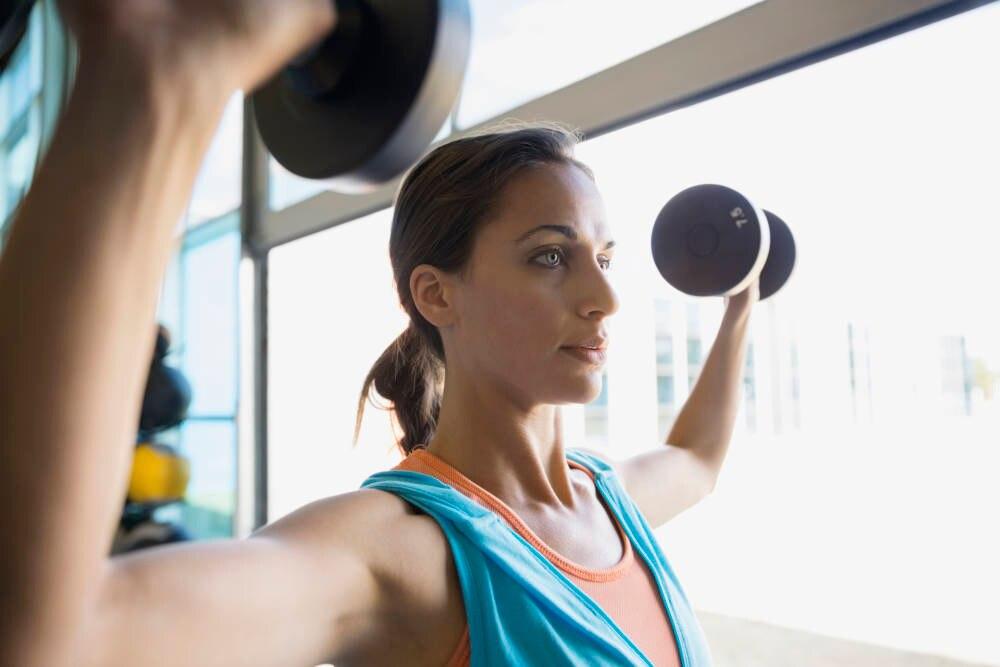 Frau macht Schulterdrücken mit Kurzhanteln zum Muskelaufbau