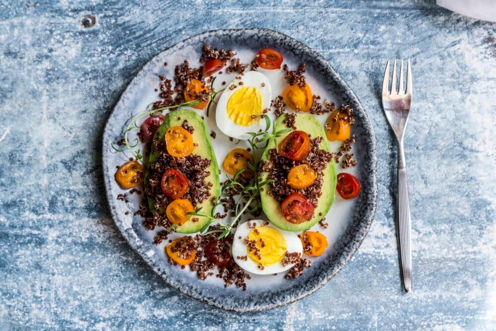 Avocado mit rotem Quinoa, Eiern und Tomaten
