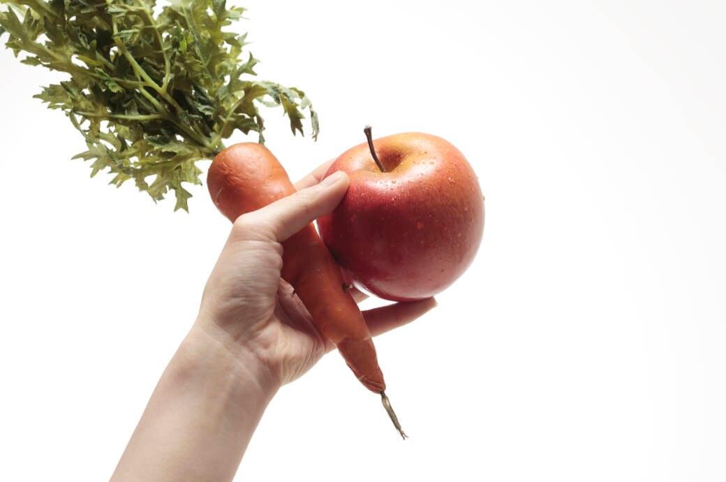 Eine Hand hält eine Möhre und einen Apfel