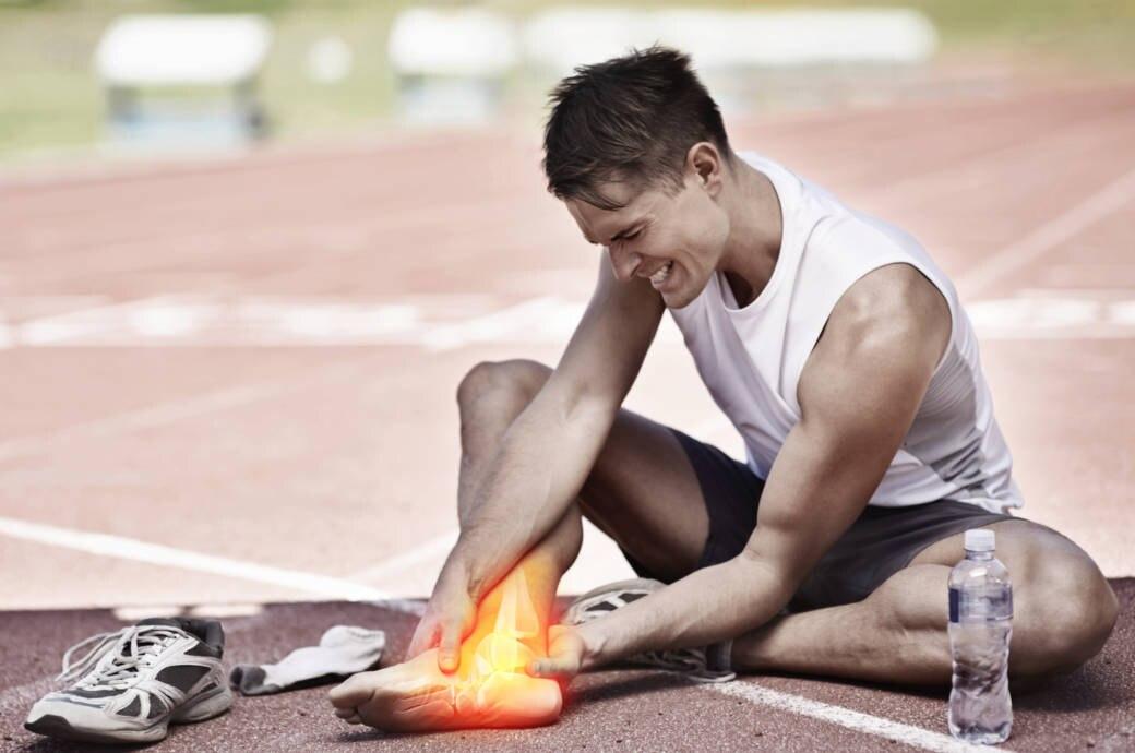 Ein junger Mann sitzt auf einer Laufbahn und hält sich seinen schmerzenden Fuß