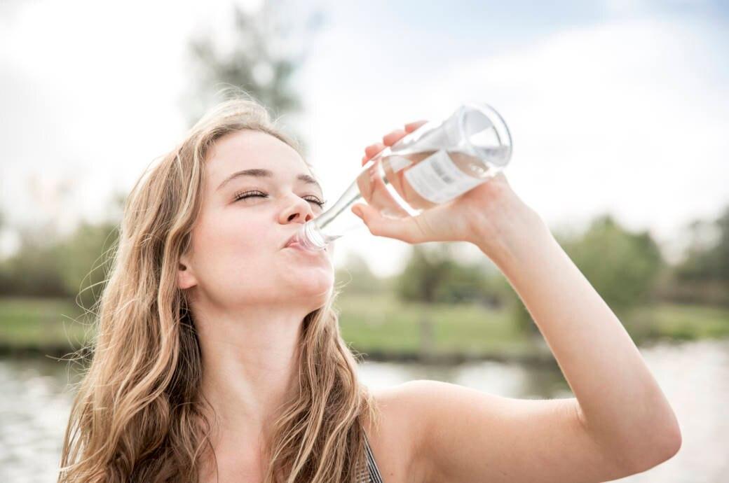 Eine junge Frau trinkt Wasser aus einer Flasche