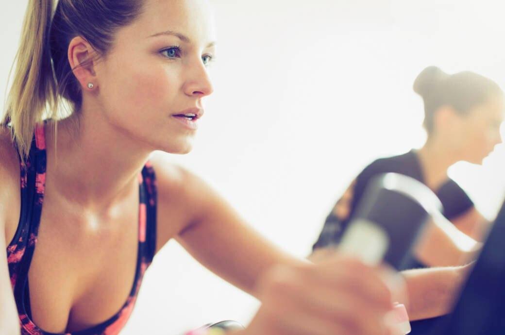 Frau trainiert konzentriert auf Ergometer