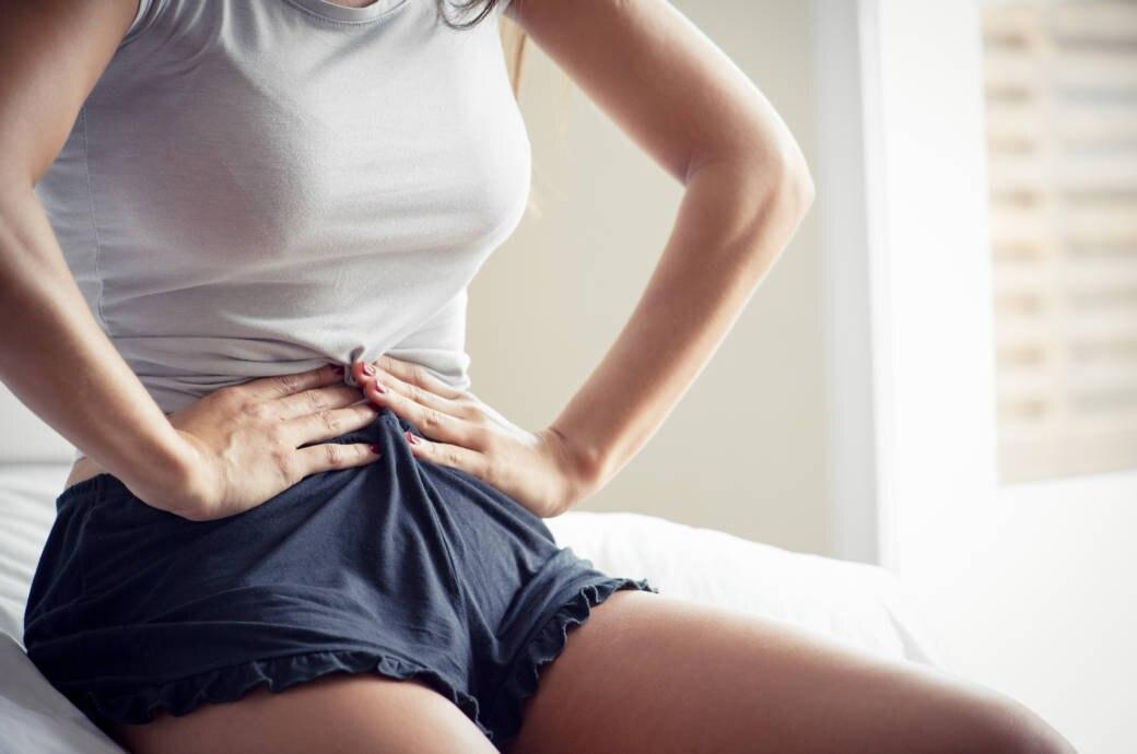 Frau hält sich den Bauch fest