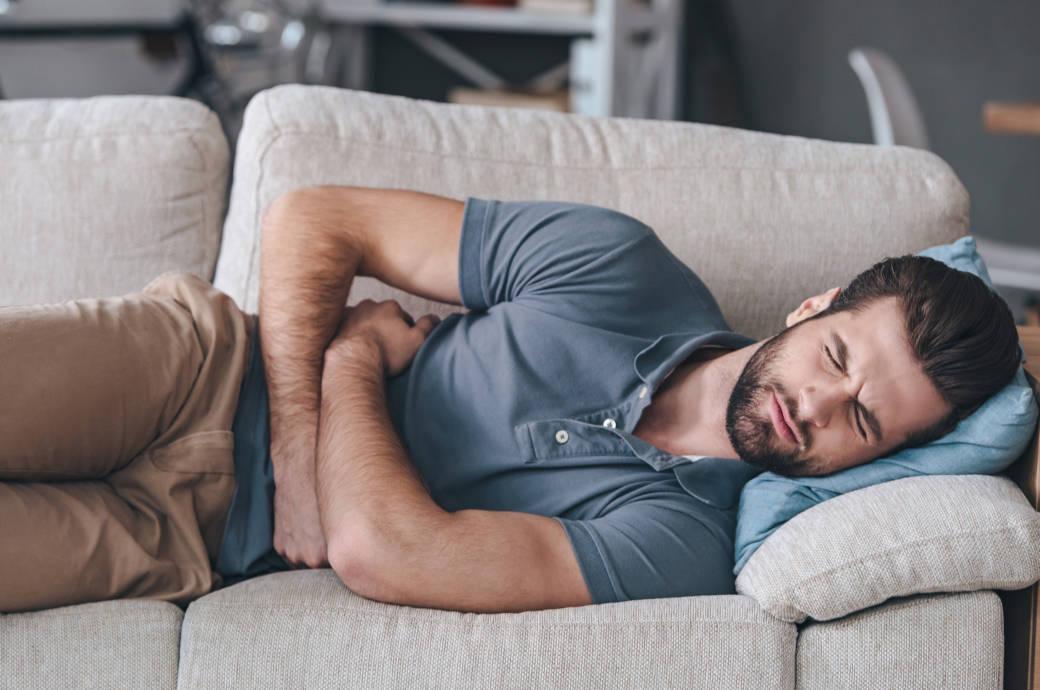 Ein Gürtelrose-Patient liegt schmerzverzerrt auf einer Couch