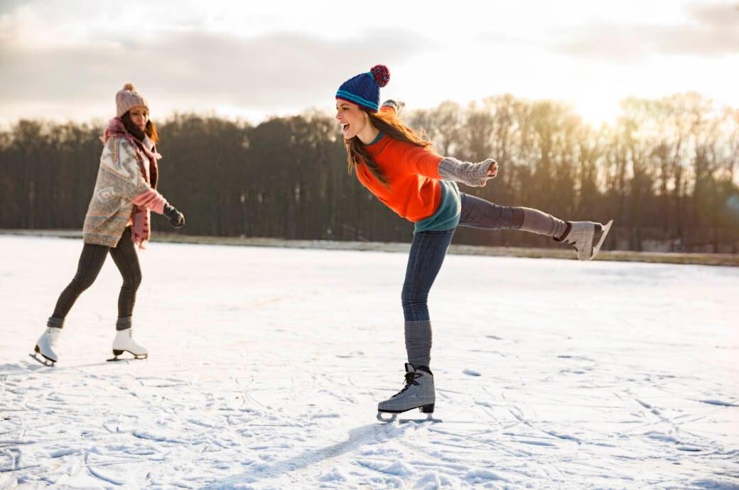 Zwei junge Frauen beim Schlittschuhlaufen auf einem See in der Sonne