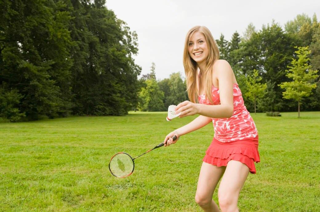 Eine junge Frau spielt Federball (Badminton)