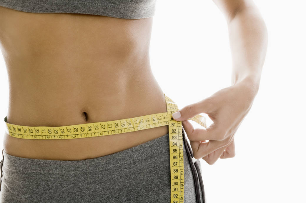 Eine Frau misst ihren Bauchumfang