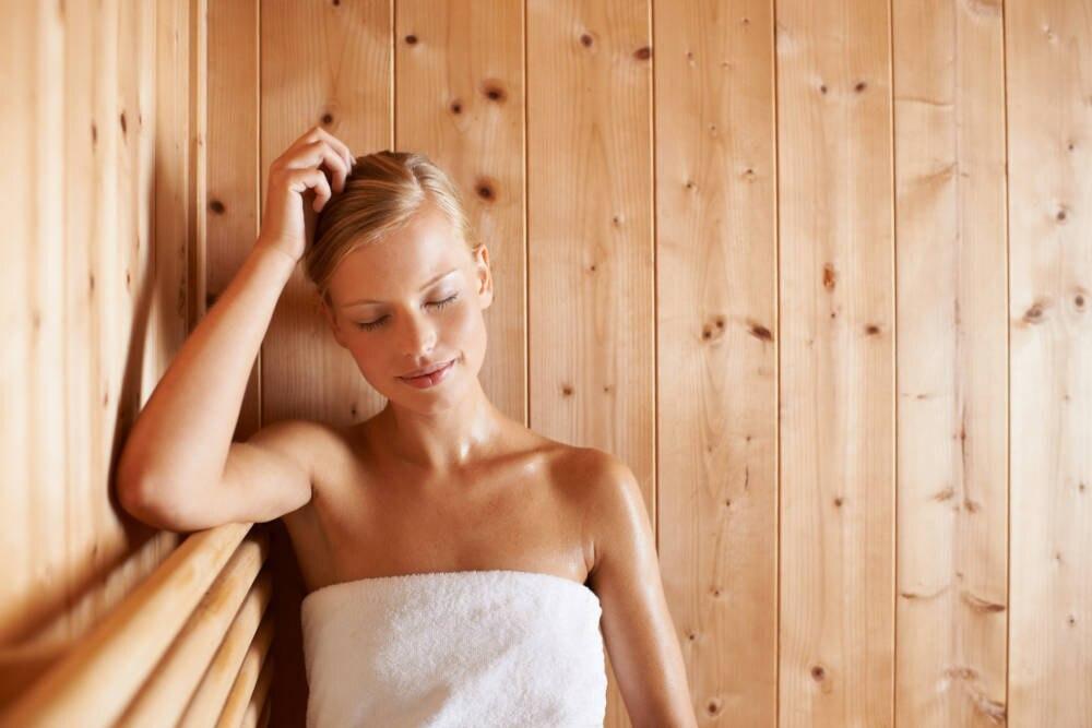 Frau mit umgeschlungenen Handtuch in der Sauna