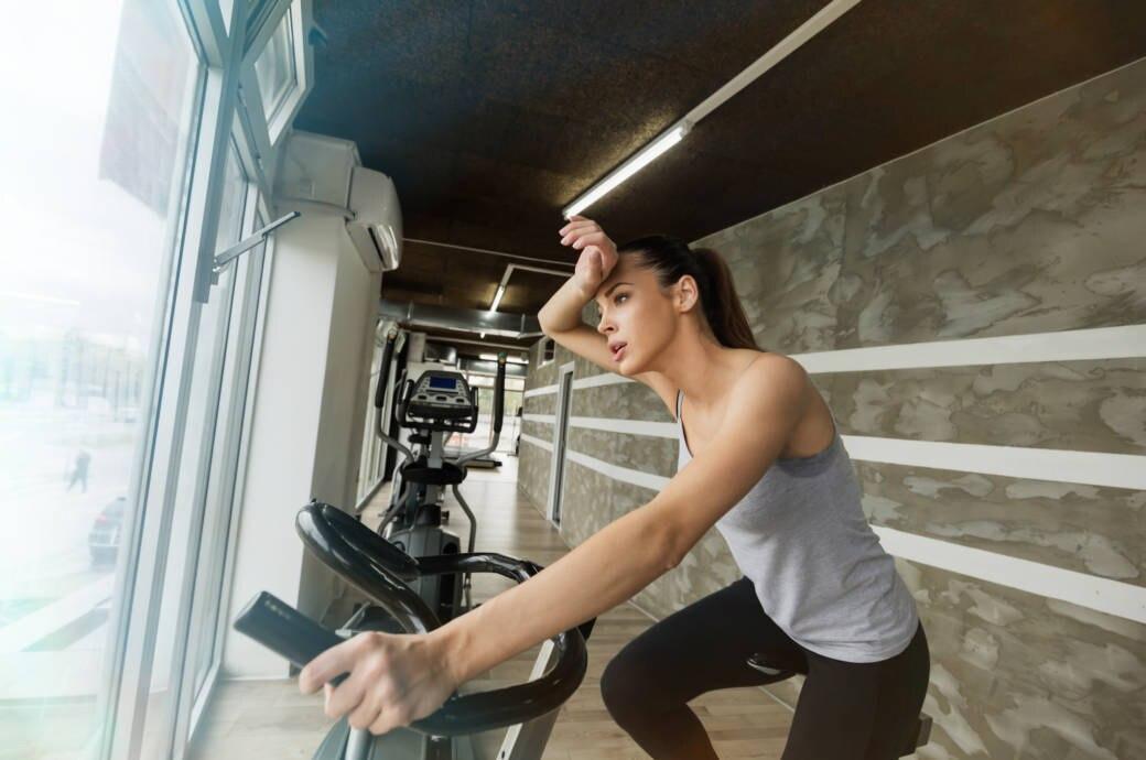 Eine Frau schwitzt beim Radfahren im Fitnessstudio