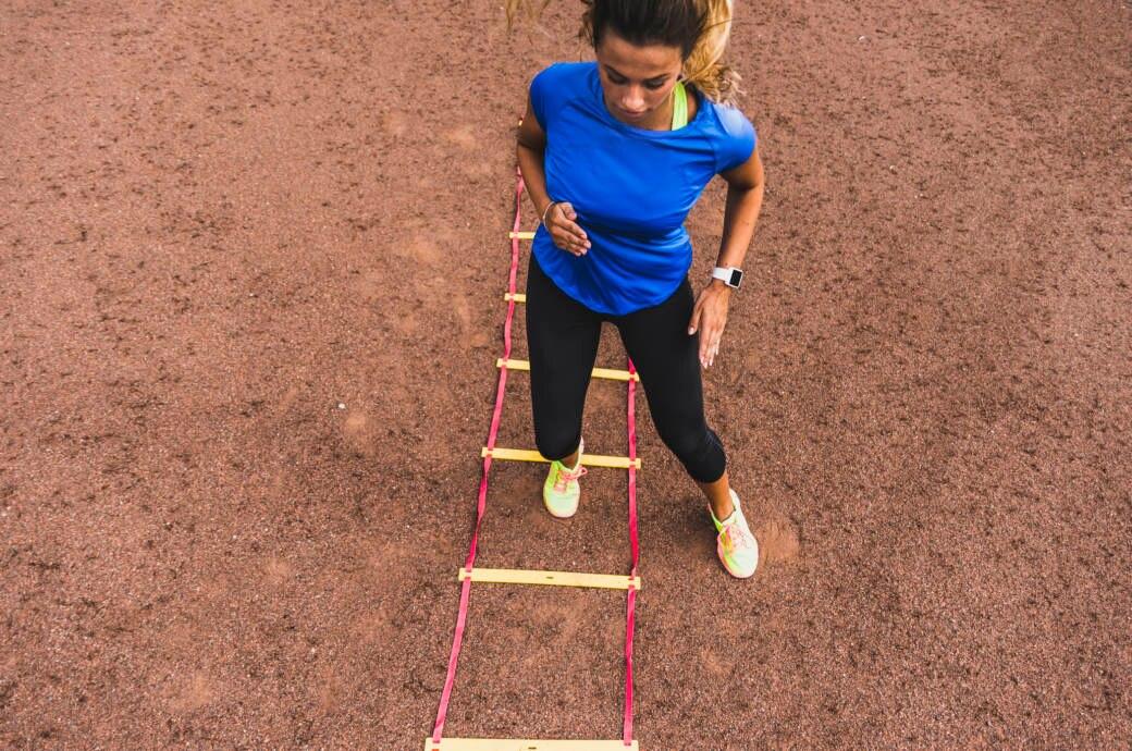 Eine Junge Frau trainiert mit der Koordinationsleiter