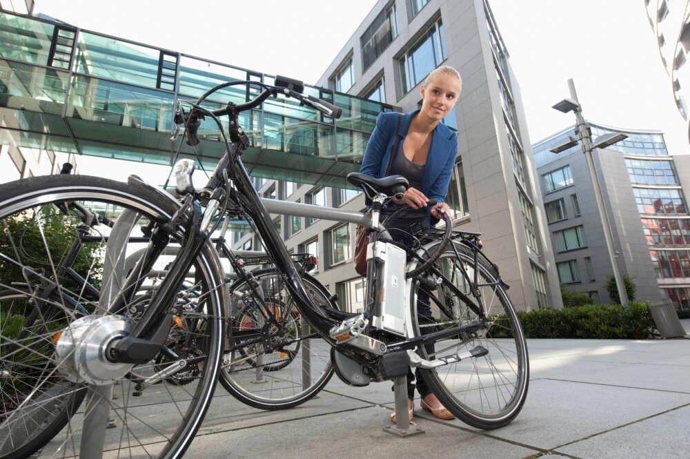 Junge Frau schließt ihr E-Bike an