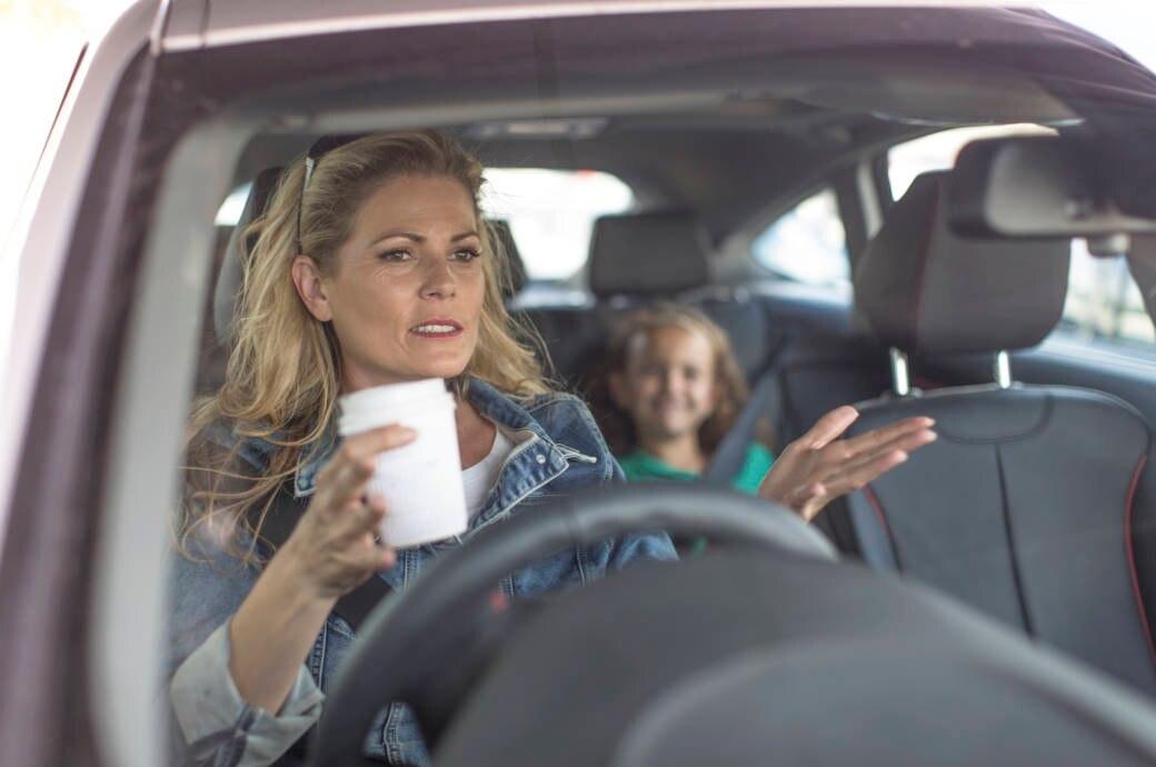 Gestresste Frau sitzt im Auto und flucht