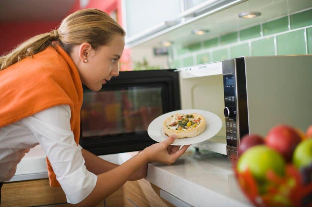 Frau bedient Mikrowelle